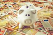 Piggy Coin Bank on fifity euro pile — Stock Photo