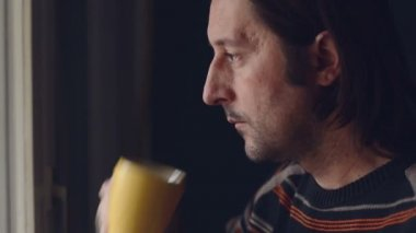 Mid adult caucasian man relaxing and drinking a cup of tea, looking out of window — Stock Video