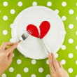 Woman eating broken heart on a white plate — Stock Photo #60755453