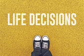 Young man standing at Life Decisions sign — Stock Photo