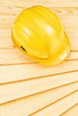 Yellow hardhat on pine wood planks — Stock Photo
