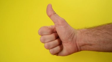 Thumbs Up For Like, male hand endorsing over yellow background — Stock Video