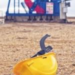 Pumpjack Oil Pump And Protective Helmet — Stock Photo #64439431