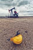 Pumpjack Oil Pump And Protective Helmet — Stock Photo