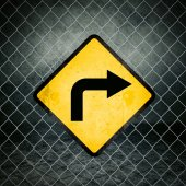 Right Direction Grunge Yellow Warning Sign on Chainlink Fence — Stock Photo