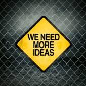 We Need More Ideas Grunge Yellow Warning Sign — Stock Photo