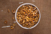 Walnut Kernels in Bowl on Brown Rustic Wood Plank Background — Stock Photo