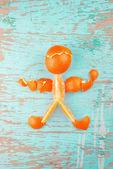 Human Figure Made of Fresh Orange Slices and Peel — Stock Photo