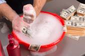 Hands are washing dollars banknotes in foam — Stock Photo