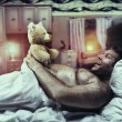 Man in bed looks at toy bear — Stock Photo #59287645