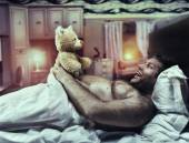 Man in bed looks at toy bear — Stock Photo