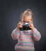 Little cute girl looks photos at the camera — Stock Photo