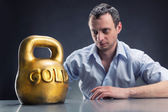 Businessman with gold kettlebell — Stock Photo