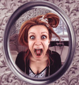 Woman looks in mirror — Stock Photo