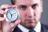 Serious businessman with clock — Stock Photo