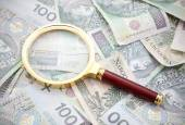 Polish money with golden magnifying glass — Stock Photo