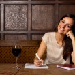 Young woman enjoying a glass of wine and writing a letter — Stock Photo #57574611
