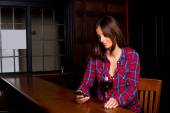 Young woman checking messages in a bar — Stock Photo