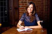 Woman writing in diary with a glass of wine. — Stock Photo