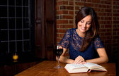 Woman reading with a glass of wine — Stock Photo