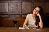 Young woman enjoying a glass of wine and writing a letter — Stock Photo