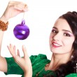 Beautiful young woman with a Christmas bauble — Stock Photo #60279717