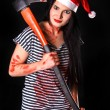 Happy young woman in a Christmas hat with a big bloody axe — Zdjęcie stockowe #61106593