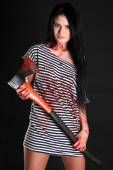 Happy young woman with a big bloody axe — Stock Photo