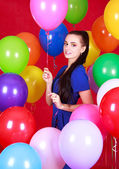 Portrait of a young attractive woman among many bright balloons — Stock Photo