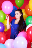 Portrait of a young attractive woman among many bright balloons — Zdjęcie stockowe