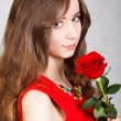 Closeup portrait of a young attractive woman with a red rose — Stock Photo #64403197