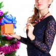 Portrait of a beautiful young woman holding a present near the C — Stock Photo #64408879
