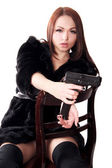Portrait of a young attractive woman with a gun — Stock Photo