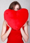 Portrait of a young attractive woman with a heart-shaped pillow — ストック写真