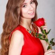 Beautiful young woman with a red rose — Stock Photo #68405609