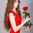 Beautiful young woman with a red rose — Stock Photo #68405649