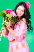 Spring portrait of a pretty young brunette with a bunch of gerbe — Stock Photo
