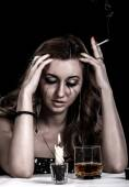 Depressed young woman with a glass of whiskey and a cigarette — Stock Photo
