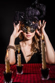 Mysterious woman in a mask near the table with alight candles — Stock Photo