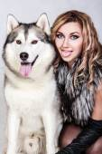 Beautiful young woman with a husky dog — Stock Photo