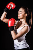 Beautiful young woman in a red boxing gloves — Stock Photo