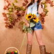 Beautiful young female farmer holding the sunflowers — Stock Photo #75460377