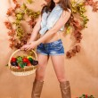 Cute young farmer girl holding the basket of vegetables — Stock Photo #75460885