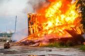 Fireman extinguishes a burning house — Stock Photo