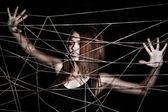 Beautiful young woman behind the interlaced ropes — Stock Photo