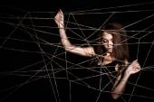 Beautiful young woman behind the net of ropes — Stock Photo