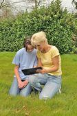 Rodzina siedzący na trawniku i za pomocą cyfrowego tabletu — Zdjęcie stockowe