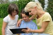 Family sitting on the lawn and using digital tablet — Stock Photo