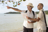 Gay couple pointing at destination — Stock Photo