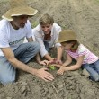 Family of farmers planting seedling — Stock Photo #53975419